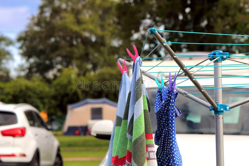 St Leonards, Hampshire, UK - May 30th 2017: Towel and swimsuit h. Anging on a rotary camping clothes drier on a campsite, with car, tent and caravan in the royalty free stock photo