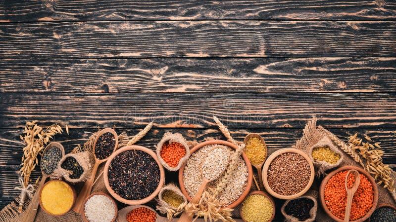 St?ll in av gryn och korn Bovete linser, ris, hirs, korn, havre, svart ris P? en svart bakgrund royaltyfria bilder