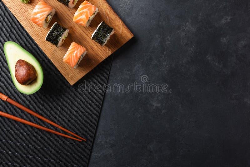 St?ll in av sushi- och makirullar med den skivade avokadot p? stentabellen royaltyfri bild