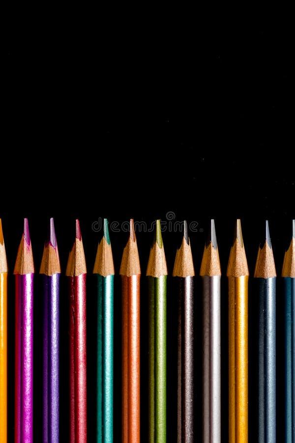 St?ll in h?rliga svarta kul?ra blyertspennor av kul?ra blyertspennor p? svart bakgrund Snart till skolan tillbaka skola till arkivbilder