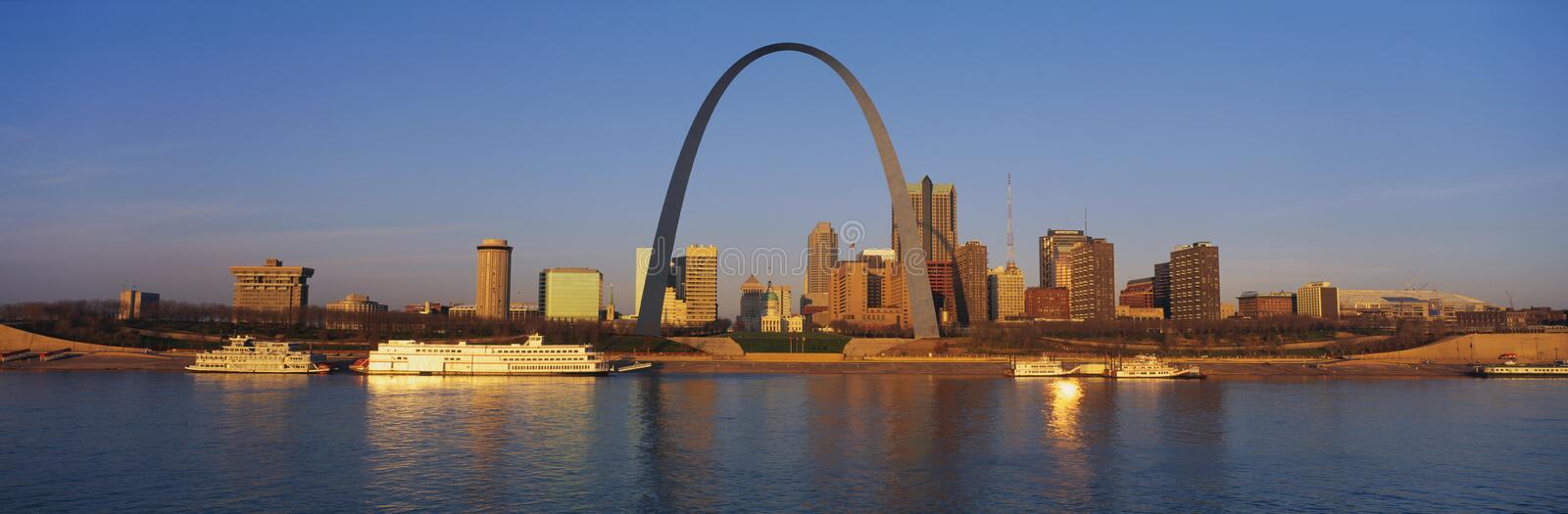 St. Louis Arch. This is the skyline at sunrise. It is situated along the Mississippi River. There are riverboats on the water with the St. Louis Arch in clear royalty free stock image