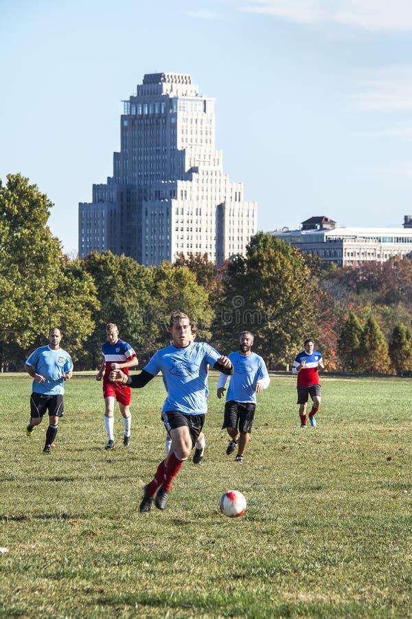 St Louis, Missouri, Estados Unidos - cerca de 2016 - homens que jogam o futebol em Forest Park com o hotel da plaza do parque da  fotografia de stock