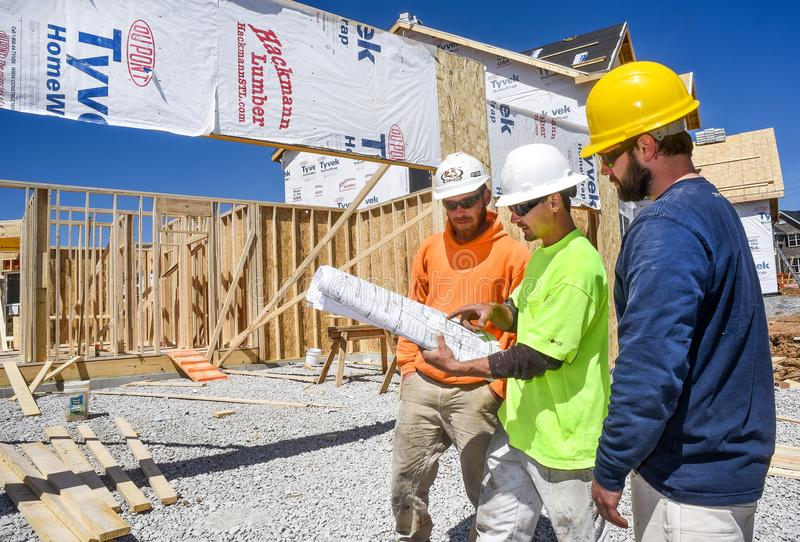St. Louis, Missouri, United States-April 4, 2018-Three male construction workers, carpenters, wearing hardhats look at blueprints royalty free stock images