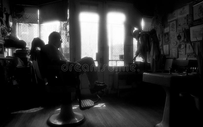 St Louis, Missouri, United States-circa 2007-Old Man Barber Sitting in Barber Chair Alone in Old Vintage Barber Shop royalty free stock images