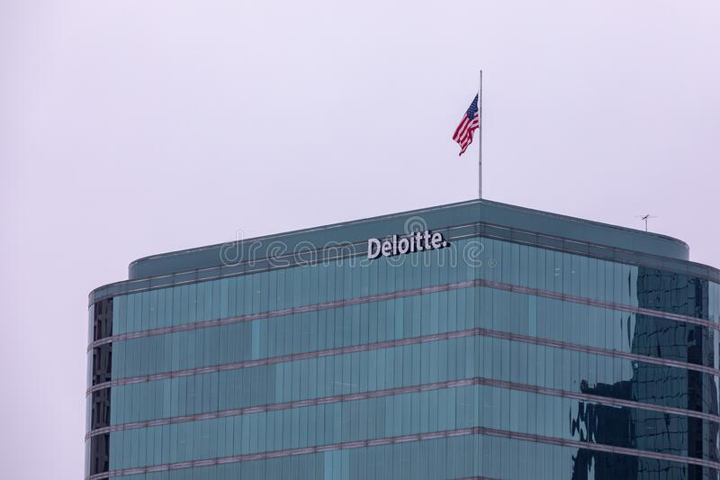 Sign of Deloitte company on a side of building with an american flag on the top royalty free stock photo