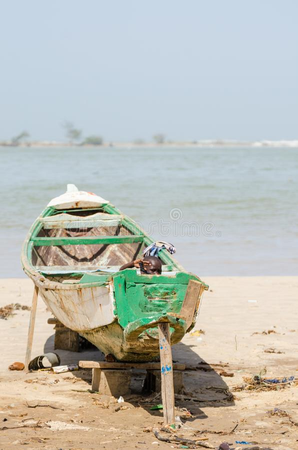 St Louis, Sénégal - 20 octobre 2013 : Jeune garçon africain non identifié se cachant dans le bateau en bois et l'ondulation images libres de droits