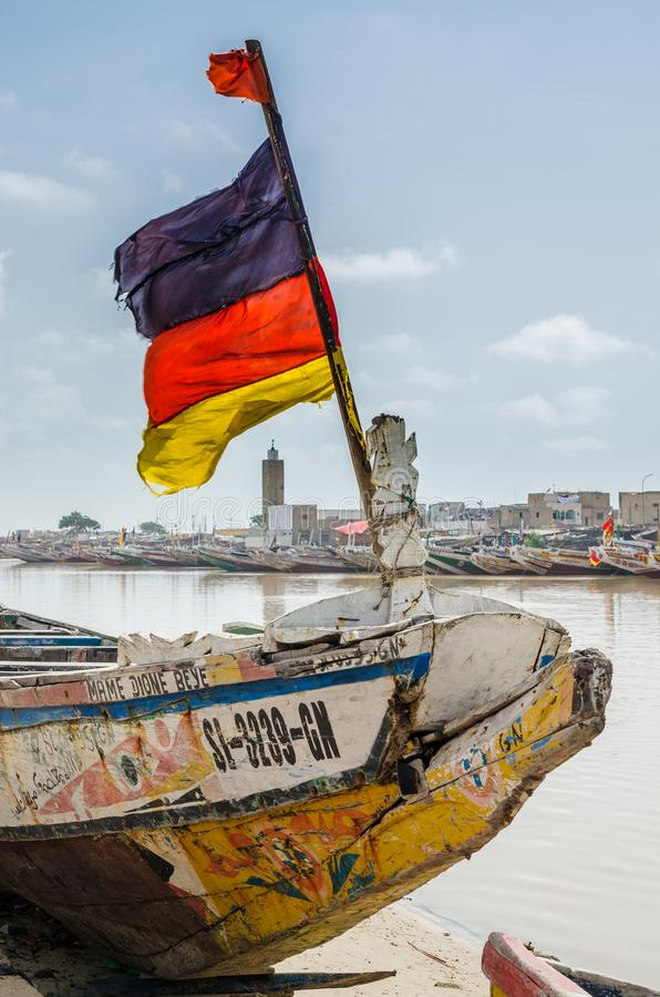 St Louis, Senegal - October 12, 2014: Colorful painted wooden fishing boat or pirogue with German flag at coast stock images