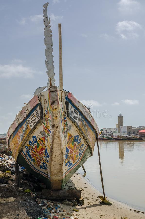 St Louis, Senegal - October 12, 2014: Colorful painted wooden fishing boats or pirogues at coast of St. Louis royalty free stock image