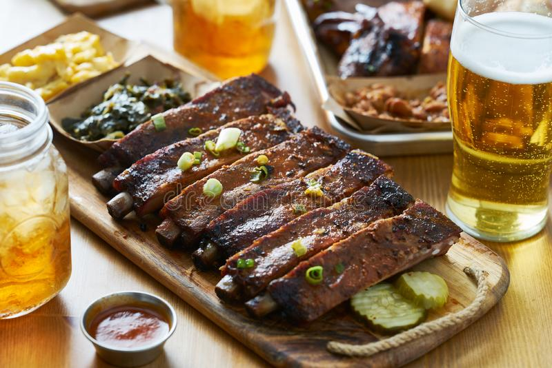 St louis style bbq ribs on table top with sweet tea, beer, collard greens and mac & cheese. Shot with selective focus stock image