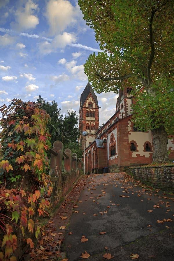 St Lutwinus kerk en weg met bladeren in Mettlach stock foto