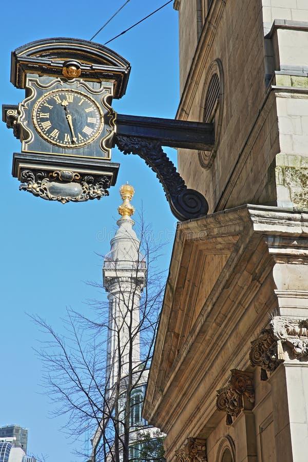 St Magnus de Martelaarkerk in het financiële district van de Stad van Londen met een klok op de linkerkant en het Monument aan stock afbeeldingen