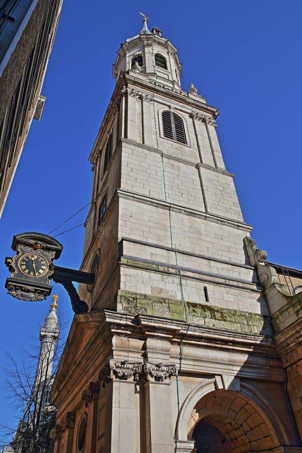 St Magnus de Martelaarkerk in het financiële district van de Stad van Londen met een klok op de linkerkant en het Monument aan royalty-vrije stock foto's