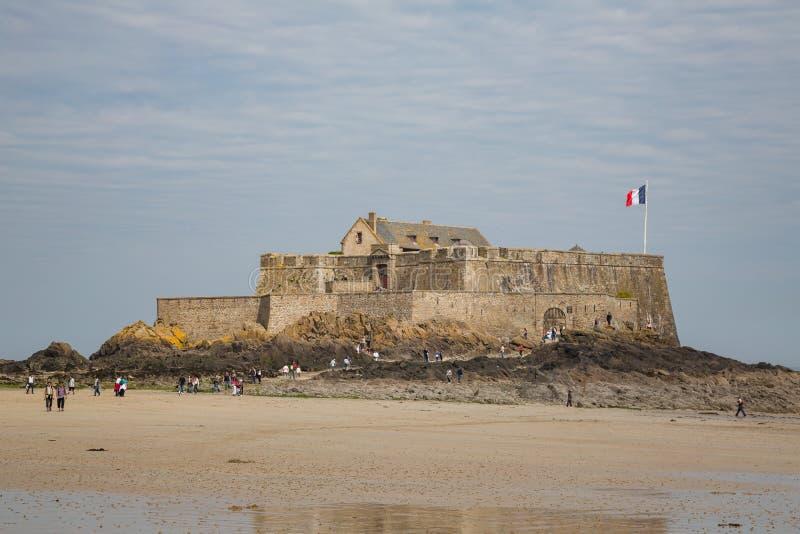 St Malo Brittany Maj 7th 2013: goście mogą chodzić mały fort na zewnątrz St Malo ścian gdy przypływ jest za obrazy stock