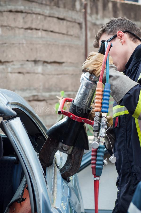 French rescue man with pneumatic machine on crashed car. St Marie aux Mines - France - 2 October 2018 - closeup of french rescue man with pneumatic machine on royalty free stock photo