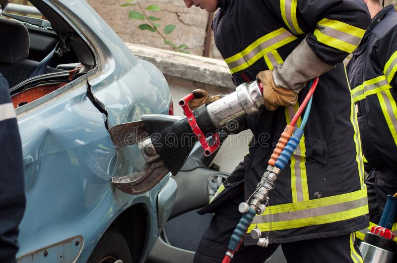 French rescue man with pneumatic machine on crashed car. St Marie aux Mines - France - 2 October 2018 - closeup of french rescue man with pneumatic machine on royalty free stock image