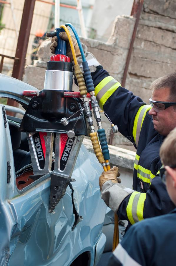 French rescue man with pneumatic machine on crashed car. St Marie aux Mines - France - 2 October 2018 - closeup of french rescue man with pneumatic machine on royalty free stock photos