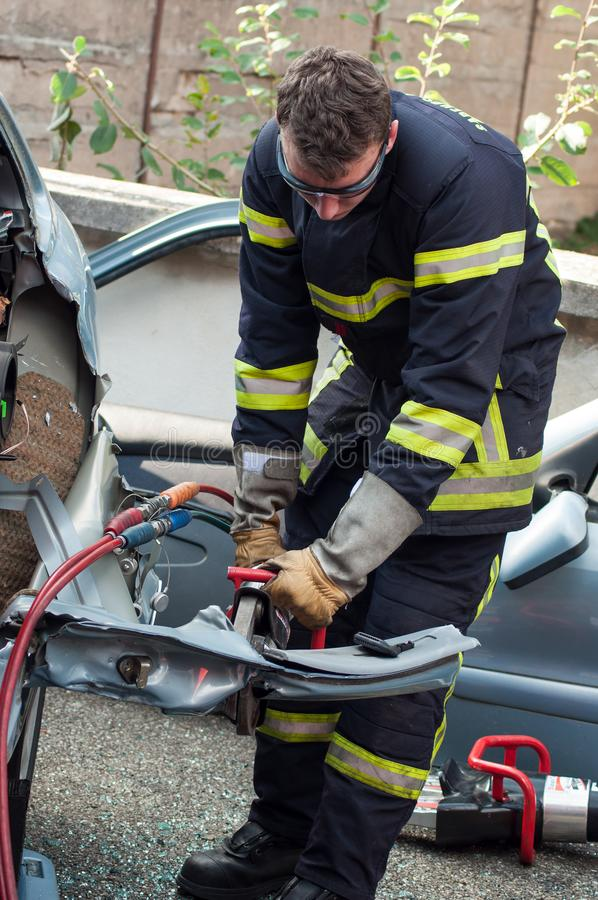 French rescue man with pneumatic machine on crashed car. St Marie aux Mines - France - 2 October 2018 - closeup of french rescue man with pneumatic machine on stock photo
