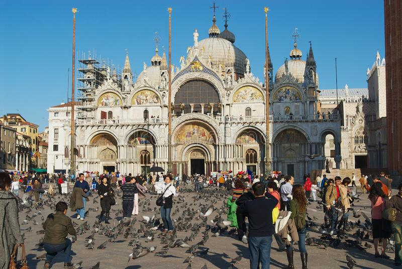 Tourists feed pigeons make photos with Saint Mark Basilica at the background at Piazza San Marco in Venice, Italy. royalty free stock photography