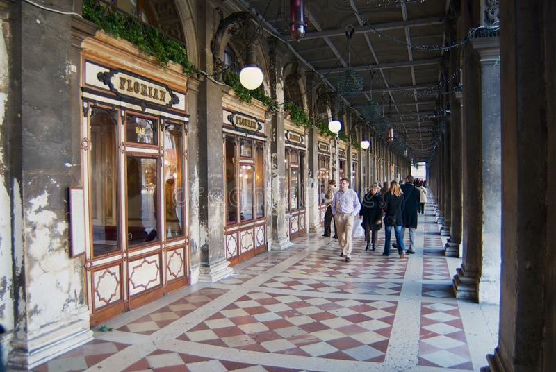 People walk by the passage in front of the windows of the famous Florian cafe at Piazza San Marco in Venice, Italy. stock image