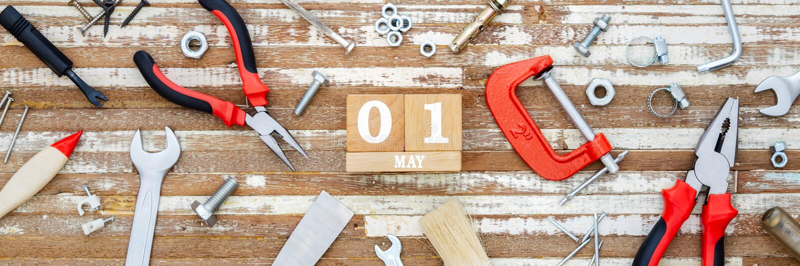 1st May. Happy International Worker& x27;s day or Labour Day Web banner background concpet.  wooden block calendar 1 May and handy. Tools on grunge wooden table stock image