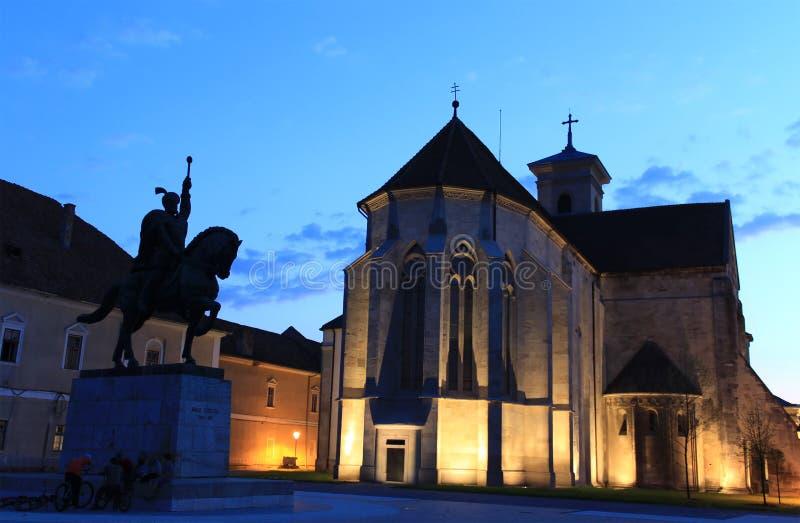 St. Michael's Cathedral in Alba Iulia, Romania. St. Michael's Cathedral (Roman Catholic cathedral) and Michael the Brave statue silhouette in Alba Iulia royalty free stock image