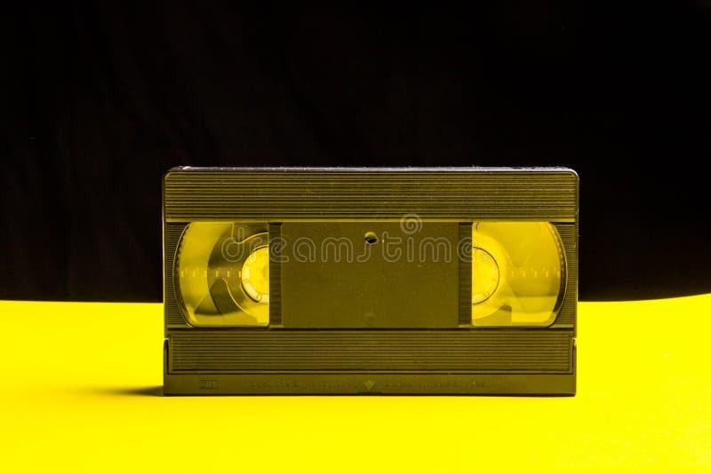 St?nde eines schwarze klassische Videobandes auf einer gelben Tabelle stockbilder