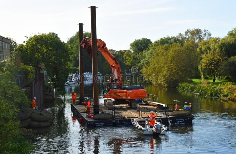 Repairs to the riverbank of the River Great Ouse at St Neots Cambridgeshire, Equipment on floating pontoon being used to drive in. ST NEOTS, CAMBRIDGESHIRE royalty free stock image