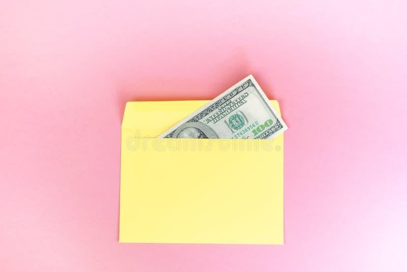 St?ng sig av pengar i gult kuvert ligger upp p? den pastellf?rgade rosa bakgrunden Br?nnm?rka upp ?tl?je; fr?mre sikt royaltyfria bilder