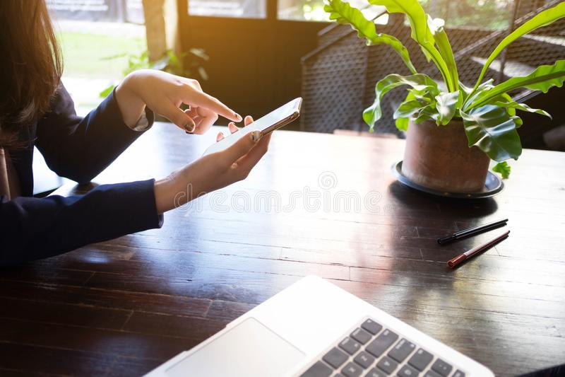 St?ng sig upp av en kvinna som anv?nder den mobila smarta telefonen p? tabellen arkivfoto