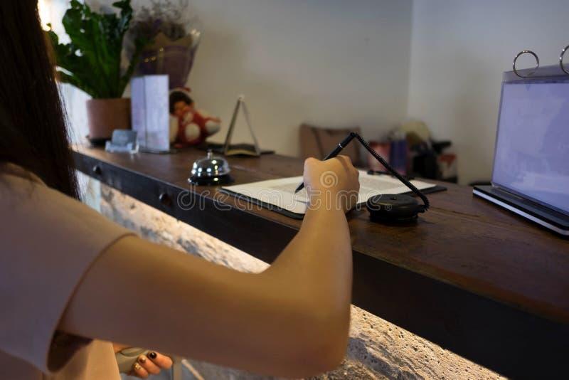 St?ng sig upp av kvinnor som s?tter undertecknings- och p?fyllningformen p? hotellmottagandet royaltyfria foton