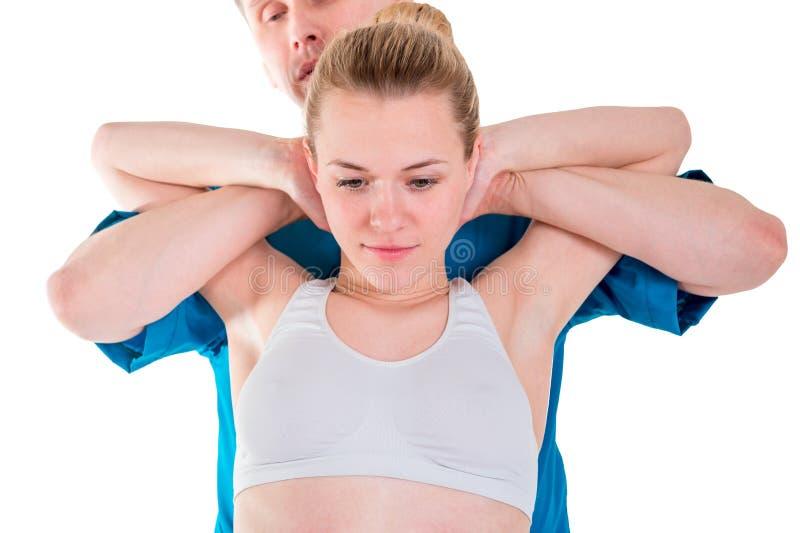 St?ng sig upp av osteopaten som g?r l?ka rotationsr?relse p? attraktiv ung kvinna Terapeut som gör tryck på flickaarmar och royaltyfri bild