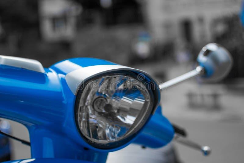 St?ng sig upp av pannlampan av en bl? klassisk sparkcykel med defocused bakgrund arkivfoto