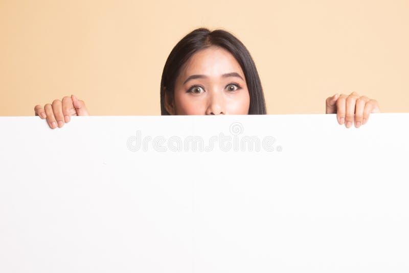 St?ng sig upp av ung asiatisk kvinna bak ett tomt tecken arkivbilder