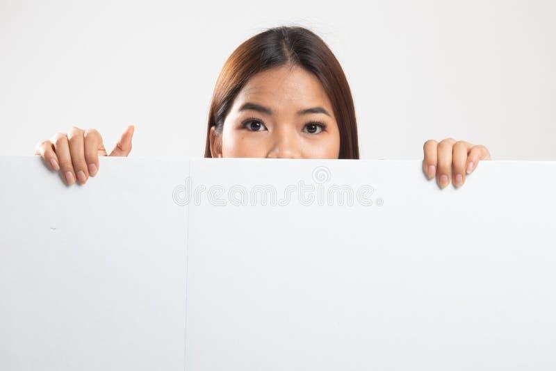 St?ng sig upp av ung asiatisk kvinna bak ett tomt tecken royaltyfri bild