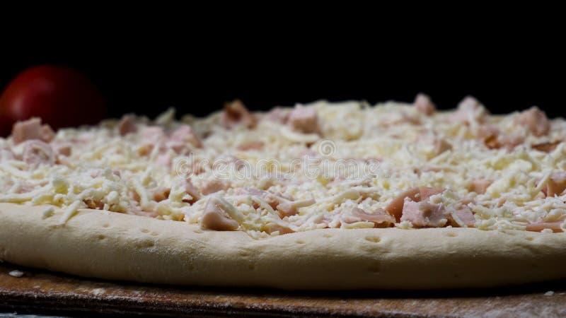 St?ng sig upp f?r kockh?nder i genomskinliga handskar som trycker p? unbaked pizza p? svart bakgrund och att laga mat begrepp Ram arkivbild