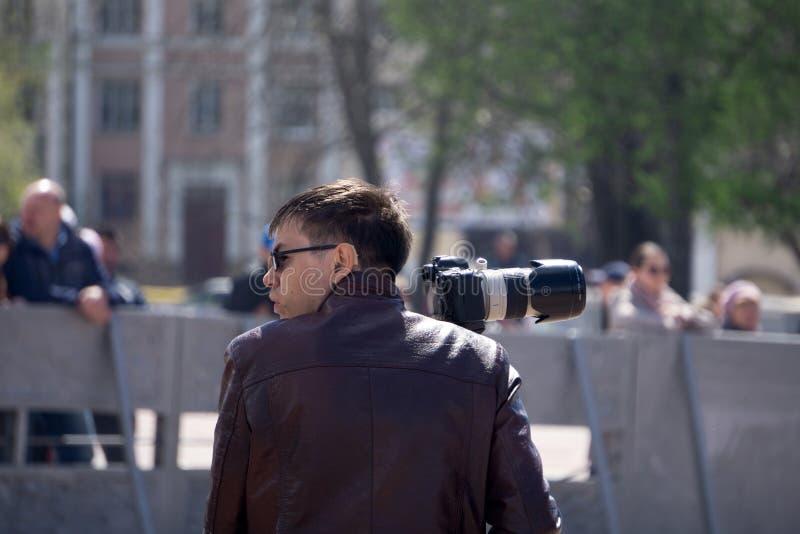 St?ng sig upp fotoet av mannen i hatt p? bl? bakgrund som tar ett foto med den digitala mirrorless kameran Ung gullig manlig foto arkivbilder