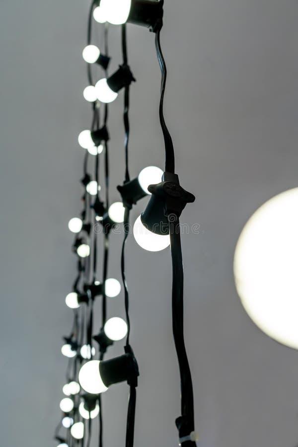 Stängt upp vita LED exponerade lightbulben med svart nylon flätad räkningskabel och förlängning på grå bakgrund royaltyfria bilder
