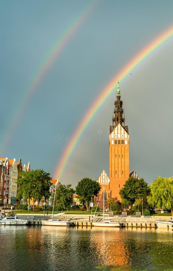 St Nicholas Cathedral med en regnbåge i Elblag, Polen arkivbilder