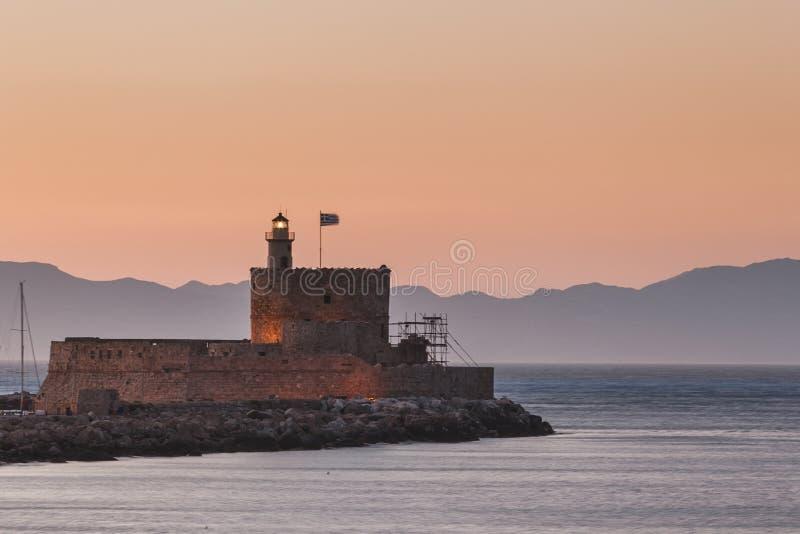 St Nicholas Fortress och fyr på solnedgången Rhodes ö Grekland royaltyfri foto