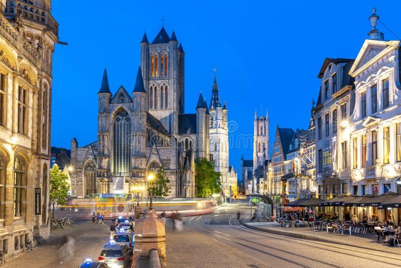 St Nicholas kyrktar, det Belfort tornet och St Bavo Cathedral på natten, herren, Belgien arkivbild