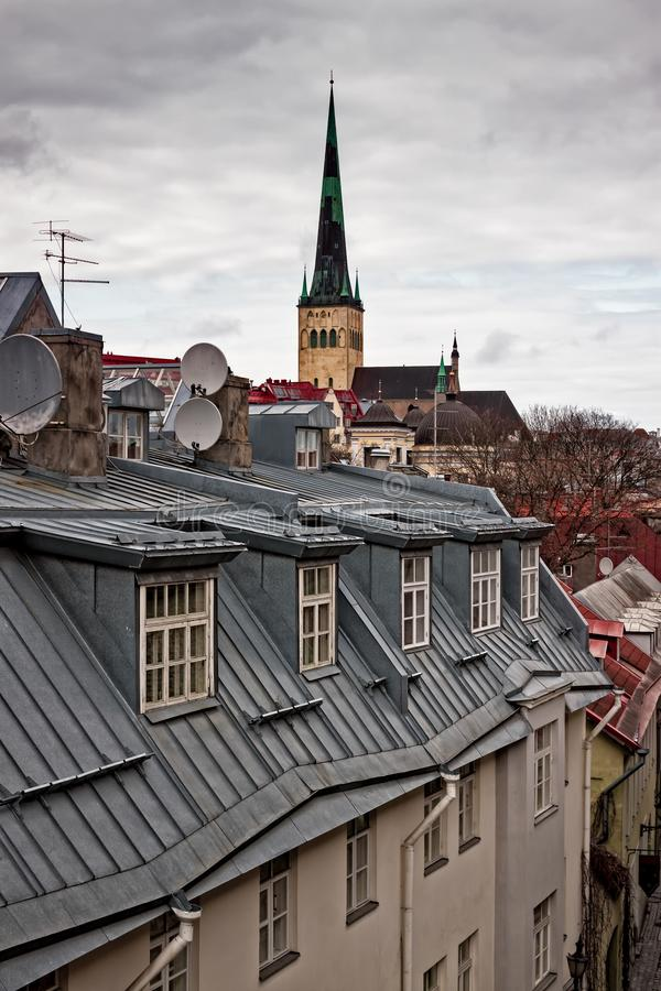 Church Behind The Houses. The St Olaf`s church in the medieval old town of Tallinn, the capital of Estonia, rises above the houses. The springtime weather is royalty free stock photography