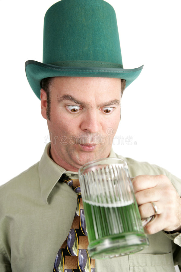 St. Paddy's Day Thirst. Man on St. Patrick's Day looking into his glass of green beer with anticipation. White background stock photo