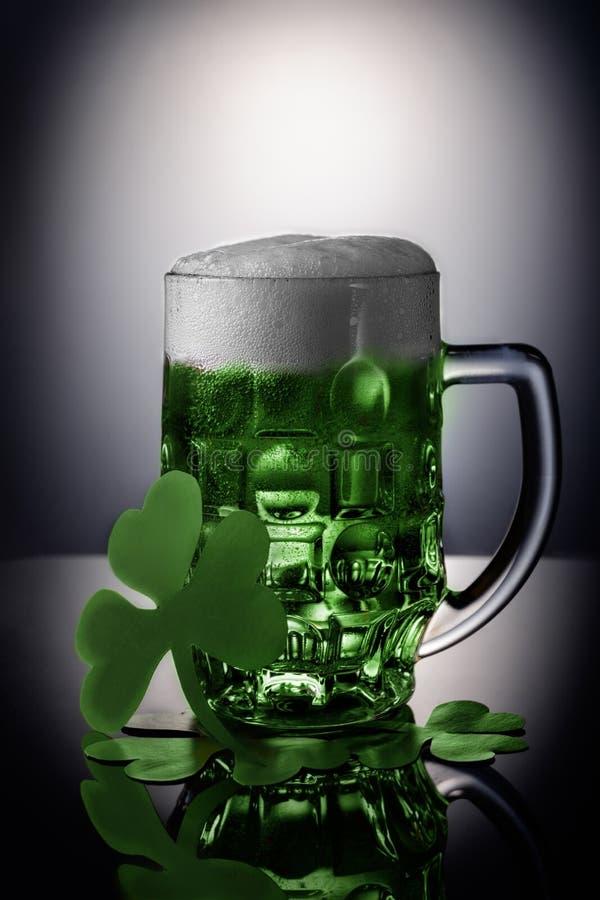 St Patrick dagconcept Glas groen bier met schuim op zwarte achtergrond met klaver royalty-vrije stock foto