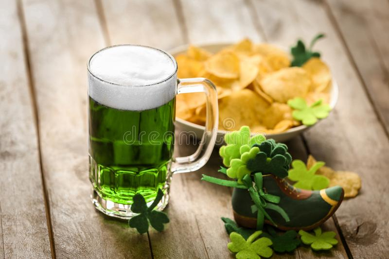 St. Patrick Day concept. Glass of green beer. And plate with crisps on wooden table stock photo