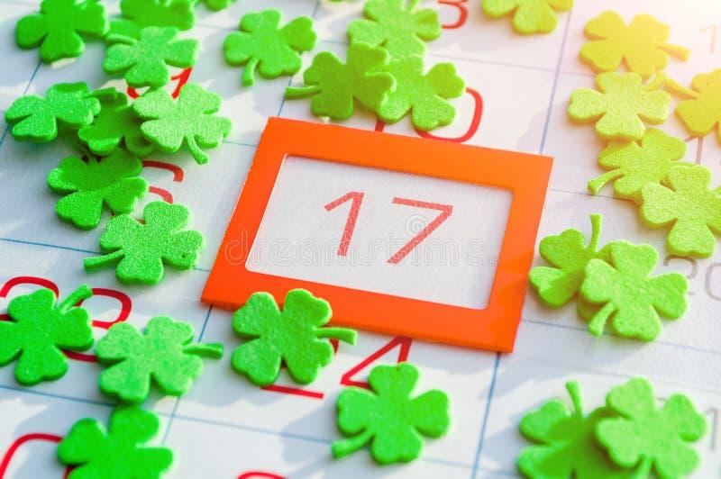 St Patrick ` s Dag feestelijke achtergrond Groene quatrefoils die de kalender behandelen met heldere sinaasappel ontwierpen 17 Ma stock afbeelding