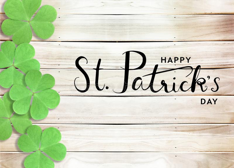 Happy St. Patrick`s Day Black Text Typography Wooden Background with Green Shamrocks clover leaf royalty free stock image