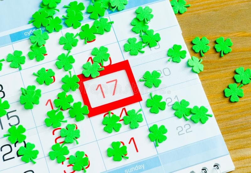 St Patrick`s Day festive background. Green quatrefoils above the calendar with framed 17 March date, St Patrick`s day. Holiday concept stock photo