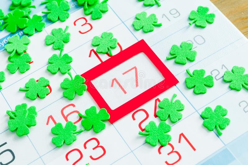 St Patrick`s Day festive background. Green quatrefoils covering the calendar with red framed 17 March stock images