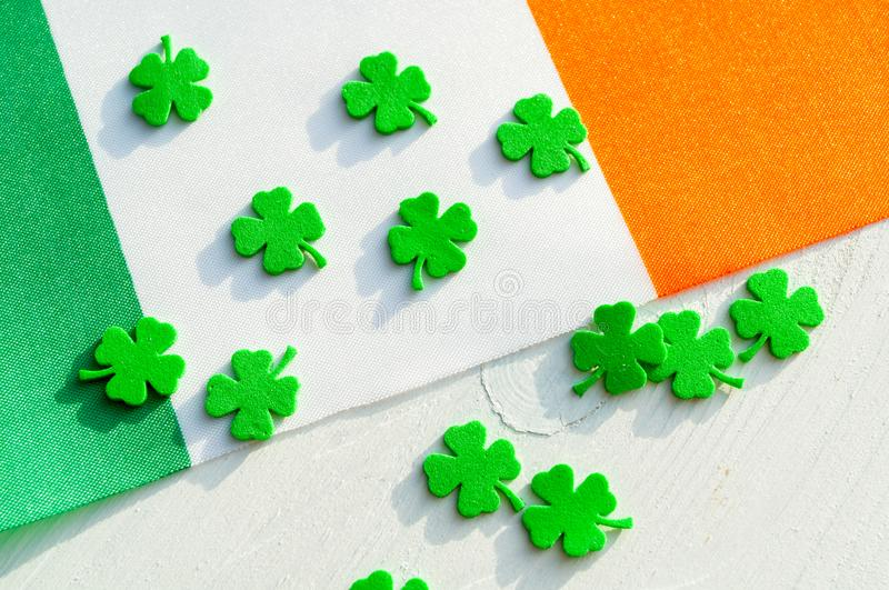 St Patrick`s Day festive background. Green quatrefoils and the Irish national flag, St Patrick`s day holiday concept royalty free stock image
