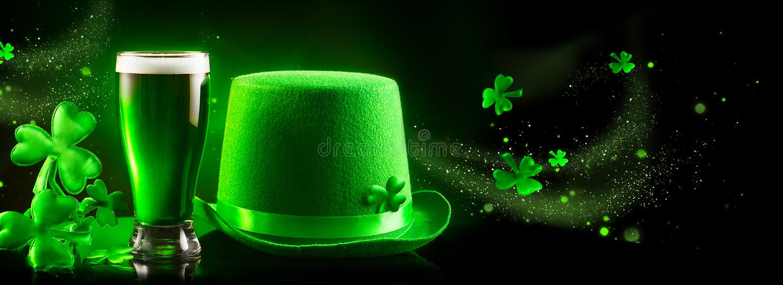 St. Patrick`s Day. Green beer pint and leprechaun hat over dark green background. Decorated with shamrock leaves. Traditional Irish festival royalty free stock photography